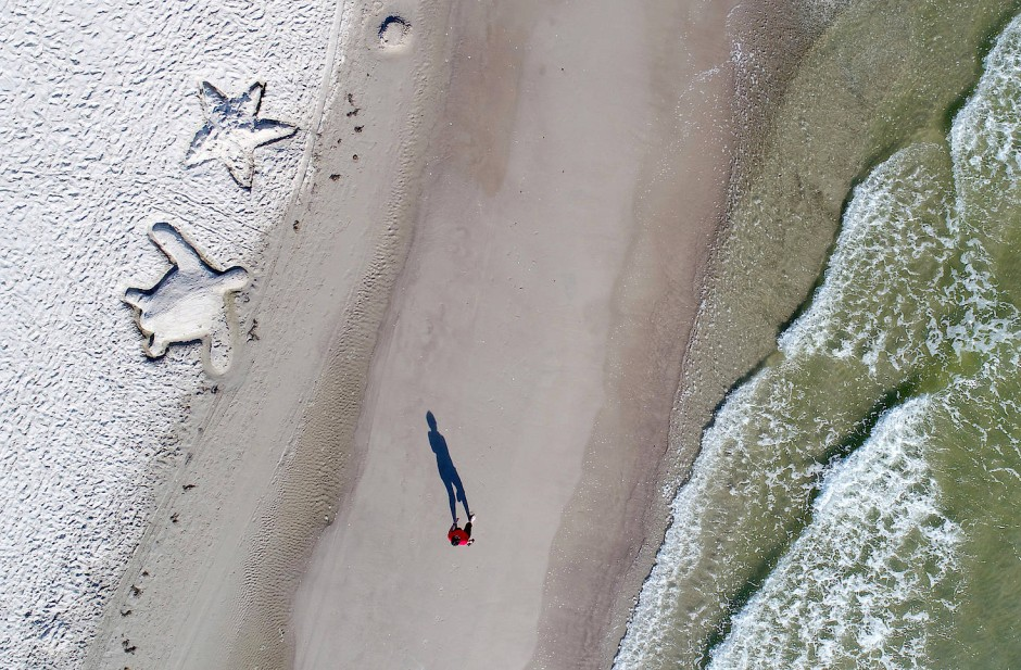 Zwei gezeichnete Sandfiguren kontrastieren den langen Schatten eines Strandläufers bei Binz auf der Insel Rügen in Mecklenburg-Vorpommern.
