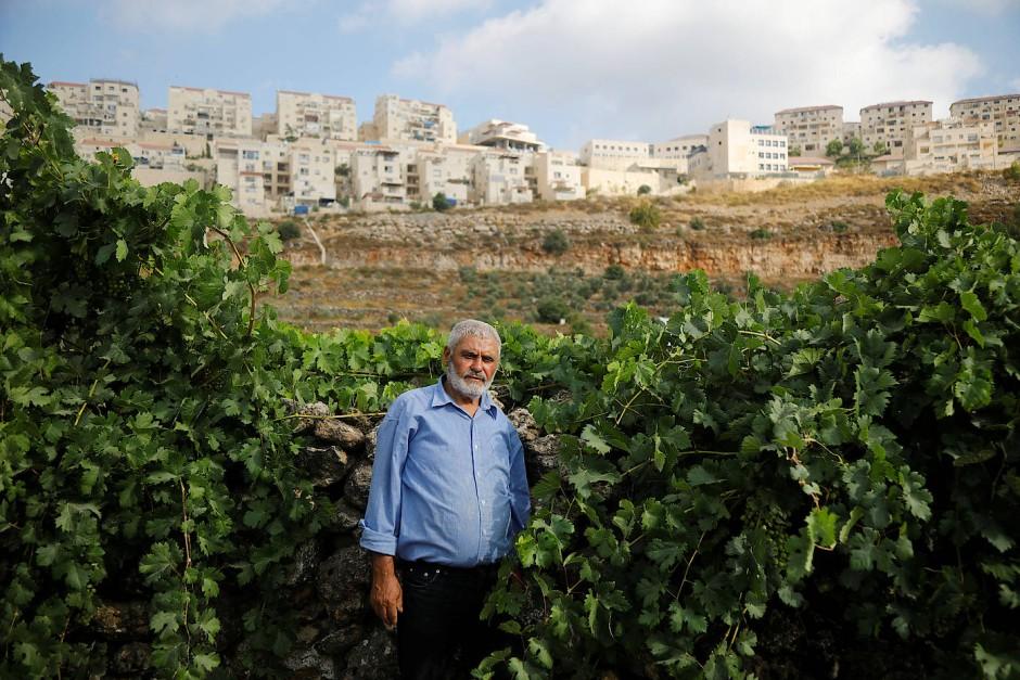 """Der  Palästinenser  Mohammad Awad aus Wadi Fukin steht vor der jüdischen Siedlung Beitar Illit.  """"Es ist unmöglich, Frieden zu haben, weil sich der Hauptkonflikt um Land dreht, das sie gewaltsam genommen haben, wie kann ich also eine Person mein Land stehlen lassen, darauf leben und es genießen, und mit ihr in Frieden leben?"""", fragt der 64-jährige."""