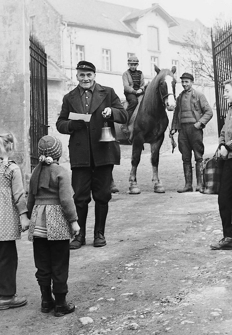 Der Schellemann – Nachrichten verbreiteten sich nur sehr langsam auf dem Land. Deshalb gab es den Schellemann oder Polizeidiener in den Dörfern. Mit seiner schweren Glocke läutete er seine amtlichen Bekanntmachungen ein, wie hier in der Schloßgasse in Sörgenloch, und verkündete die neuesten Nachrichten, überwiegend aus dem Ortsgeschehen. Er war eine kleine Sensation, nicht nur für die Kinder, sondern auch für die Erwachsenen. (Foto 1957)