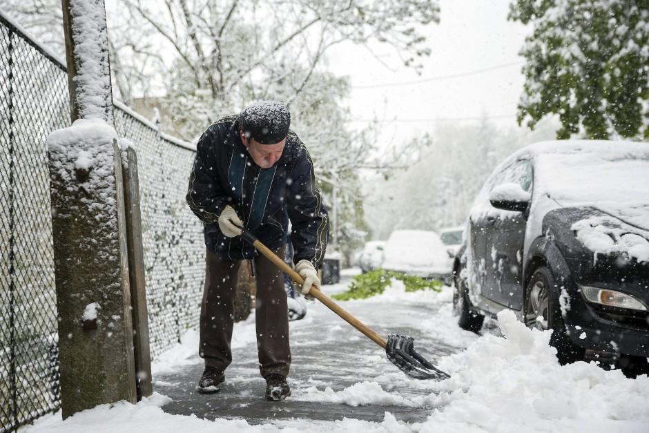 Ein Mann schaufelt am Mittwoch in Ungarns Hauptstadt Budapest Schnee vom Bürgersteig. Schneefälle führten im Süden des Landes zu Verkehrsbehinderungen und Stromausfällen.