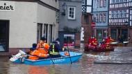 Mitarbeiter der Feuerwehr bergen Bewohner aus den vom Wasser eingeschlossenen Häusern in der überfluteten Altstadt des hessischen Büdingen.