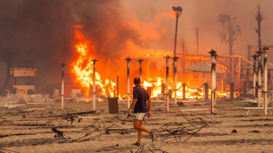 """Sonnenschirme und Liegen brennen am Strand """"Le Capannine"""" in Catania, nachdem sich ein Waldbrand auf Sizilien bis hierher ausgebreitet hat."""
