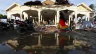 Eine Fußgängerin geht am am Samstag an einem zu Teilen eingestürzten Gebäude in Aceh an der Nordwestspitze der Insel Sumatra vorbei.