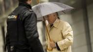 Der frühere PP-Schatzmeister Luis Bárcenas versteckt sich am Montag in Madrid unter einem Regenschirm.