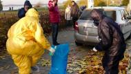 Mitarbeiter des Veterinäramtes ziehen am Sonntag ihre Vollschutzkleidung nach einem weiteren Fund am Cospudener See in Markkleeberg (Sachsen) bei Leipzig aus.