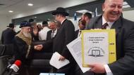 Der Araber Hussein Dschabar (rechts) hält die Vertragsunterlagen über den Kauf der Brotvorräte des Staates Israel für das jüdische Pessach-Fest in der Hand. Im Hintergrund schütteln sich Oberrabbiner Izchak Josef (links) und Oberrabbiner David Lau die Hände.