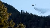 Ein Hubschrauber löscht am Montag in Kochel am See (Bayern) ein Feuer am Jochberg. Brandursache war wohl ein Lagerfeuer.