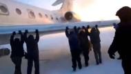 Passagiere schieben festgefrorenes Flugzeug an