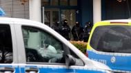 Polizisten stehen am Mittwochmorgen vor einem Bürokomplex im hessischen Dietzenbach. Hier und an vielen anderen Orten haben sie nach Waffen, Munition und Drogen gesucht.