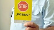 Dieter Schäfer, Leiter der Verkehrspolizeidirektion Mannheim, zeigt am Montag bei einer Pressekonferenz in Mannheim Posern die gelbe Karte.
