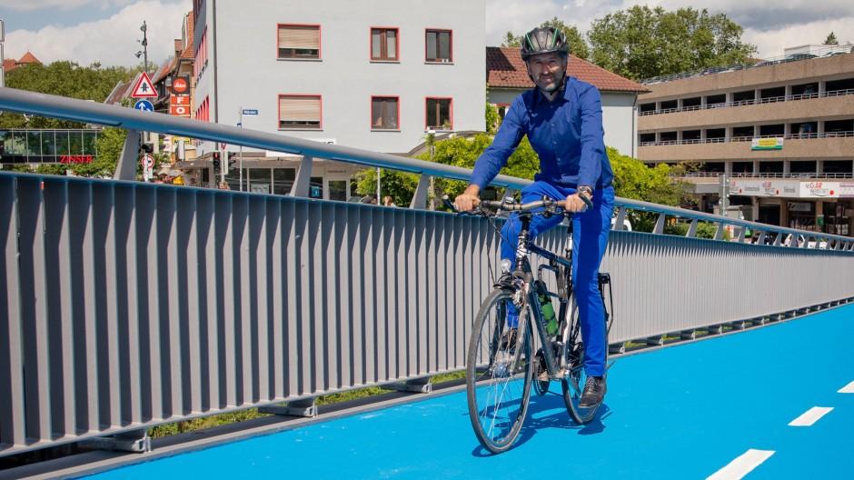 Boris Palmer fährt mit seinem Fahrrad über eine neu eröffnete beheizbare Radbrücke in Tübingen.