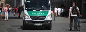 In der Münchner Fußgängerzone schiebt am Samstagmorgen ein Mann sein Fahrrad an einem Polizeiwagen vorbei. Weniger Menschen als sonst sind am Tag nach der Schreckensnacht mit zehn Toten in der Stadt unterwegs.