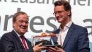 Hendrik Wüst, neuer Vorsitzender der CDU in NRW, überreicht seinem Vorgänger Armin Laschet als Geschenk ein Modell eines Sportwagens.