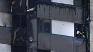 Ein Feuerwehrmann begutachtet am 14. Juni die entzündbare Fassadenverkleidung am ausgebrannten Grenfell Tower in London.