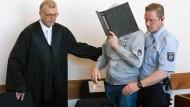Der Angeklagte Andreas V. wird von Justizmitarbeitern in den Saal des Landgerichts in Detmold geführt.