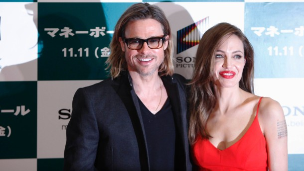 """U.S. actor Brad Pitt and his partner Angelina Jolie pose during the Japan premiere of Pitt's film """"Moneyball"""" in Tokyo"""