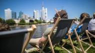Junge Männer sitzen am Freitag in Frankfurt in Liegestühlen am Mainufer.Samstag und Sonntag soll das Wetter noch sommerlicher werden.