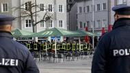 Am Königsplatz in Augsburg: Zwei Polizisten stehen unweit der Trauerveranstaltung der Feuerwehr für das Opfer der Gewalttat vom Freitagabend.