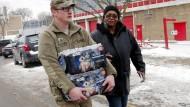 Ein Soldat hilft einer Bewohnerin von Flint, Wasserflaschen in ihre Wohnung zu tragen. Das Trinkwasser  der Stadt ist mit Blei verseucht.