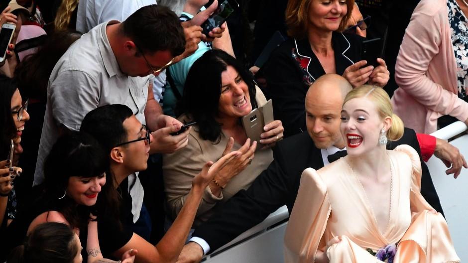 Weiß, wie man die Fans glücklich macht: Schauspielerin Elle Fanning posierte in ihrer Cape-Robe für Selfies auf dem roten Teppich.