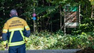 Bayern, Waldmünchen: Ein Feuerwehrmann steht an einem Wanderweg auf der Suche nach dem vermissten Mädchen.