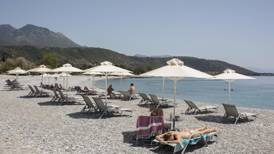 Touristen genießen den Ritsa-Strand in Kardamyli, einer Stadt am Meer, fünfunddreißig Kilometer südöstlich von Kalamata.