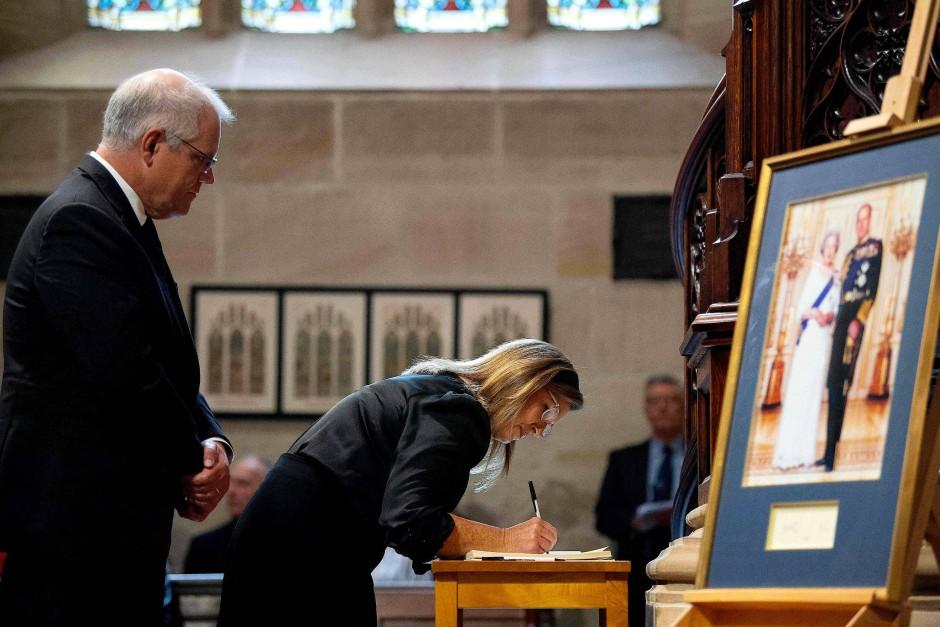 Australiens Premierminister Scott Morrison (links) und seine Frau unterschreiben im Kondolenzbuch in der St Andrew's Kathedrale in Sydney.