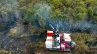 Gefahr durch Munitionsreste: Ein Löschfahrzeug spritzt Wasser in das Moor, das im Untergrund brennt.