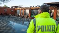 Ein Polizist steht am Donnerstag im niedersächsischen Echem vor der abgebrannten Grundschule des Ortes.