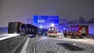 Feuerwehr und Rettungwagen stehen am Donnerstag an einem Unfallort auf der A9, bei dem ein Sattelzug auf schneebedeckter Fahrbahn die Kontrolle verloren hat und in die Mittelleitplanke gerutscht ist.