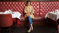 Im Restaurant Forlini's an der Baxter Street: Goldener bestickter Kurzmantel von Dolce & Gabbana, Jeans von Fiorucci, Sandalen in Beige und Schwarz von Giorgio Armani.