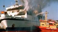 Unglücks- oder Tatort? Am 8. April 1990 versuchen Löschboote im Hafen Lykesil die Flammen auf der Scandinavian Star zu ersticken.