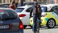 Ein Fahrradfahrer fährt im April in Rostock hinter parkenden Autos entlang. Der Radweg, den es an dieser Stelle gab, wurde entfernt.