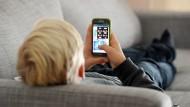 Ein Junge surft mit dem Smartphone. Bislang gab es bei Kommunikationsdiensten kaum Jugendschutz (Archivbild).