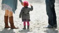 Ein Kind steht am auf einem Spielplatz in München zwischen seinen Eltern (Archivbild). Wer die Kinder seines Partners adoptieren möchte, muss dafür verheiratet sein.