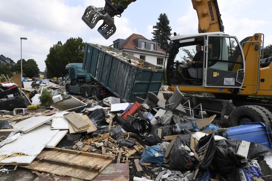 Abtragen der Müllberge: In Opladen belädt nach der Flut ein Bagger einen Container mit Abfall.