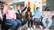 Schülerinnen einer siebten Klasse in Frankfurt haben zum ersten Mal nach Monaten wieder gemeinsam Präsenzunterricht bei ihrem Klassenlehrer.