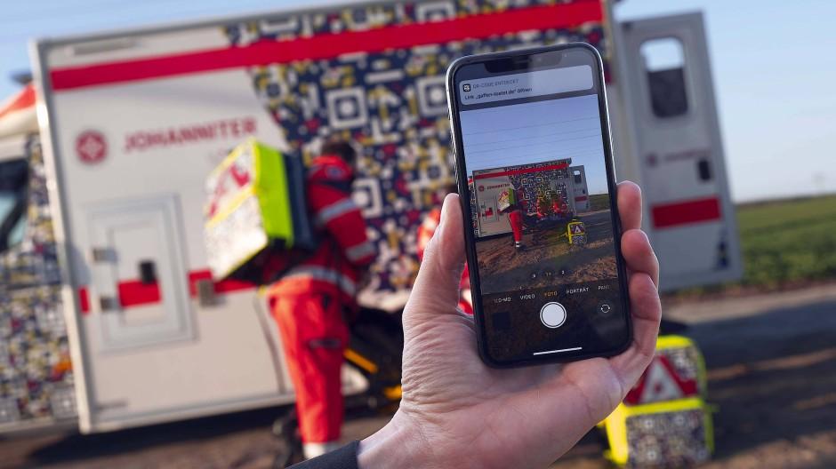 In einer gestellten Szene der Johanniter ist auf einem Smartphone der QR-Code auf einem Rettungswagen zu sehen, der die Botschaft «Gaffen tötet» enthält.