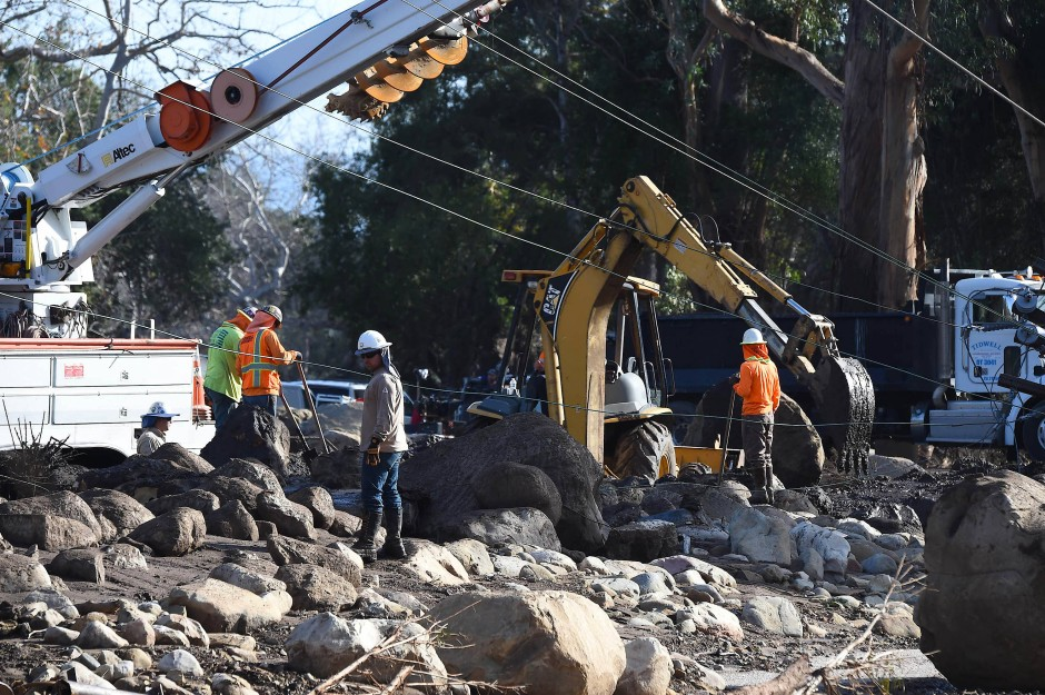 Arbeiter räumen am Mittwoch in Montecito Geröll von einer Straße.