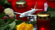 Ein Flugzeug-Model im März 2015 zwischen Blumen und Kerzen vor der Unternehmenszentrale von Germanwings in Köln. Ein Jahr später wollen Schüler aus Haltern wieder nach Barcelona fliegen.