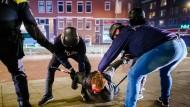 In Rotterdam nehmen Polizeibeamte während der Krawalle einen jungen Mann fest.