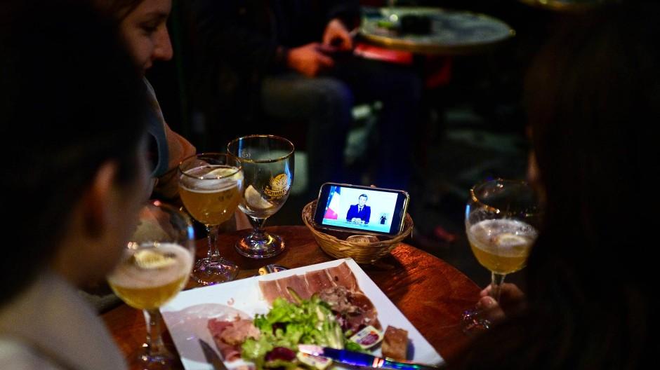 Besucherinnen eines Pariser Cafés schauen Präsident Macrons Ansprache auf einem Smartphone.