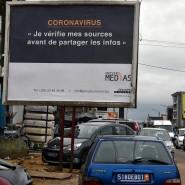 """Bürger im ivorischen Abidjan gehen an einem Schild mit der Aufschrift: """"Coronavirus: Ich prüfe die Quellen, bevor ich Informationen verbreite"""" vorbei"""