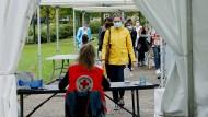 In einer Teststation im französischen Bayonne warten mehrere Menschen auf ihre Corona-Abstriche.