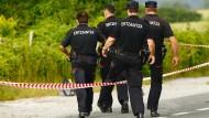 Polizisten steigen am Fundort einer Frauenleiche in Nordspanien über eine Absperrung.