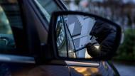 Ein Mann versucht in einer gestellten Szene, eine Autotür mit einer Metallstange aufzubrechen. Die Zahl der Autodiebstähle befindet sich auf einem Rekordtief.