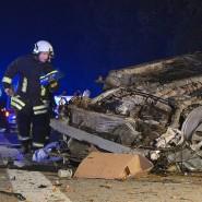 Ein Feuerwehrmann inspiziert auf dem Seitenstreifen der A7 das Wrack, das von dem Familienwagen übrig geblieben ist.