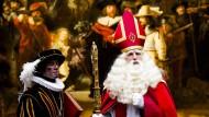 """Der niederländische """"Sinterklaas"""" und sein traditioneller Begleiter, der """"schwarze Peter"""" (l.)"""