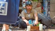 """Reiner Schaad, besser bekannt als """"Eisenbahn-Reiner"""" sitzt mit seiner Spielzeugsammlung in einer Straße nahe der Frankfurter Zeil."""
