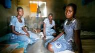 Unsichere Unterkunft: Mary, Evelyn und Gladys (von links) in ihrer Hütte - Mitschülerin Salomey ist krank und liegt im Hintergrund auf ihrer Matte.